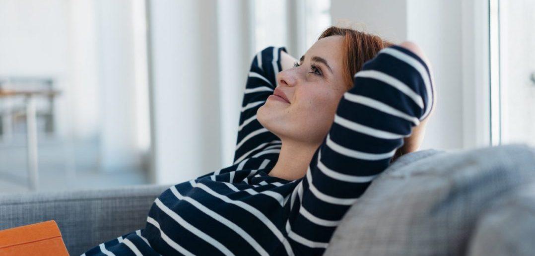 Women relaxing on grey sofa