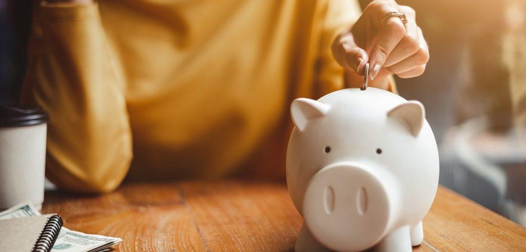 Putting money in white piggy bank