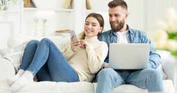 Young couple on sofa using laptop and mobile phone