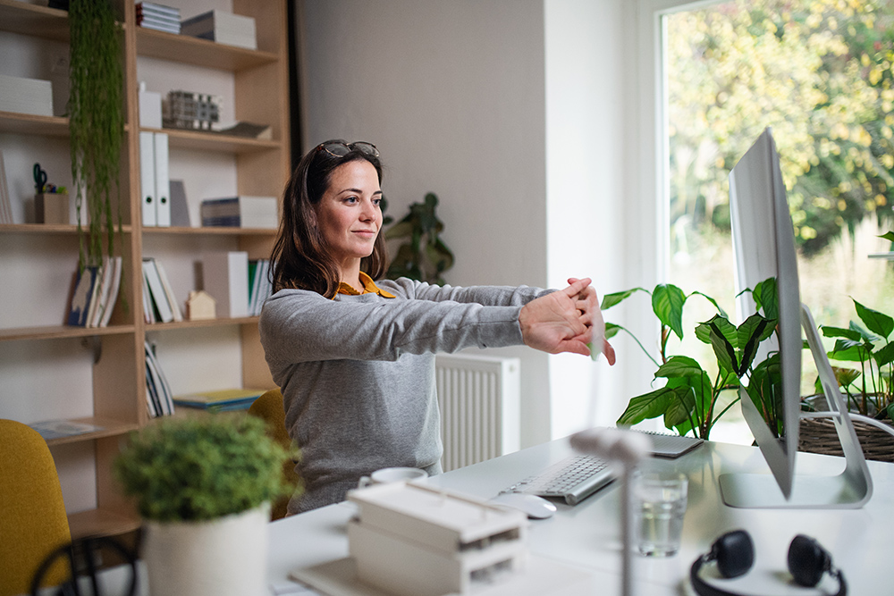 Women sat at desk in home office with plants and window