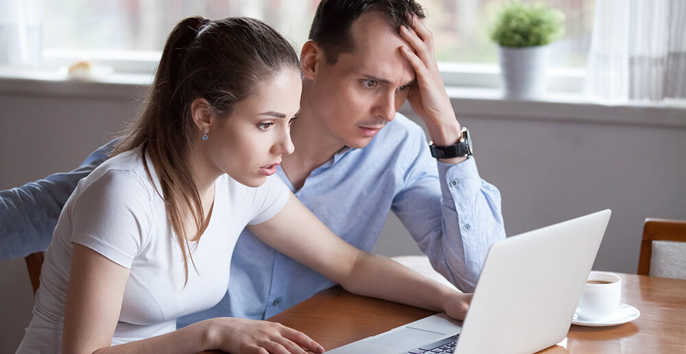 Couple looking worried and stressed whilst using laptop