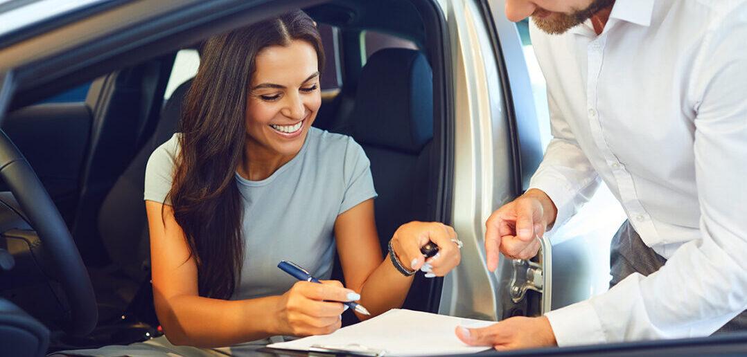Women in car. Women buying car. Women signing agreement for car purchase.