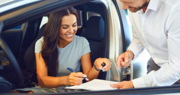 Women in car. Women buying car. Women signing agreement for car purchase.
